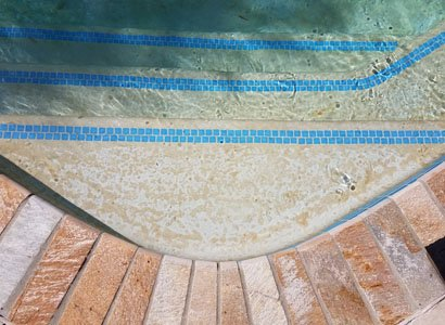 Poway pool with old stained and damaged plaster