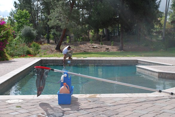 Adding-chlorinetabs-during-pool-cleaning-service