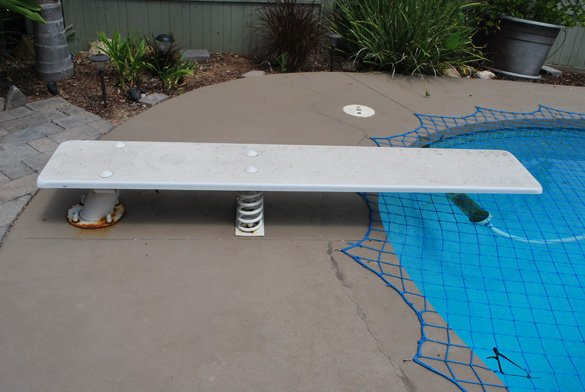 swimming pool with a diving board and safety net