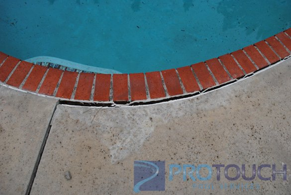 concrete deck with red pool coping brick