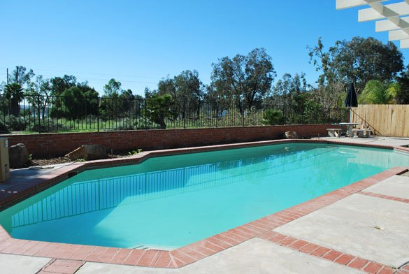 backyard pool with brick and concrete deck