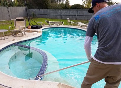 Cleaning blue pool tile during service