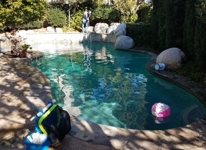 Cleaning the pool floor with vacuum attachment