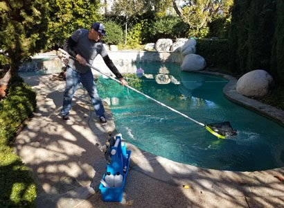 Cleaning the surface of swimming pool in carmel valley