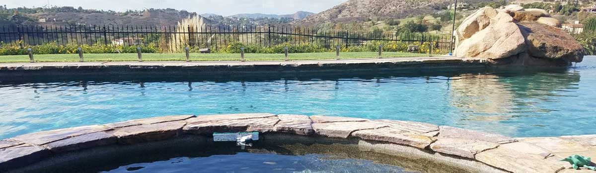 Pebble swimming pool with artificial stone water features
