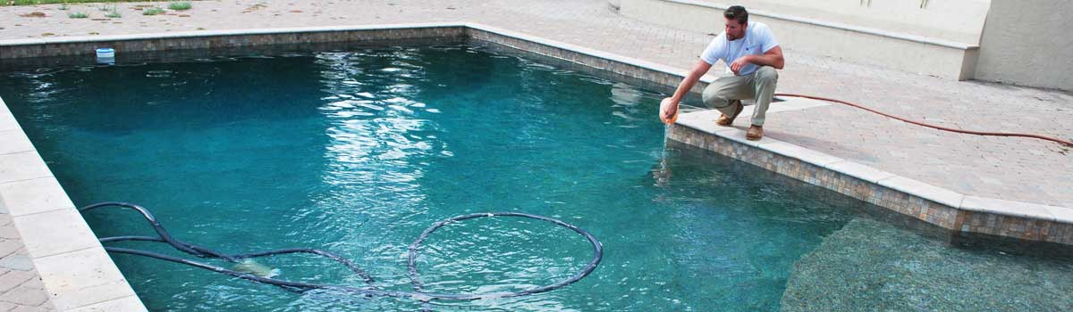 Pool Cleaningtechnician ading chemicals during this Escondido pool service visit